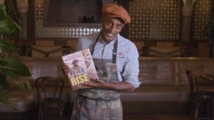 Marcus Samuelsson holding The Rise cookbook.